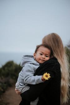 Jonge jongen die een bloem houdt die door zijn mamma wordt gedragen