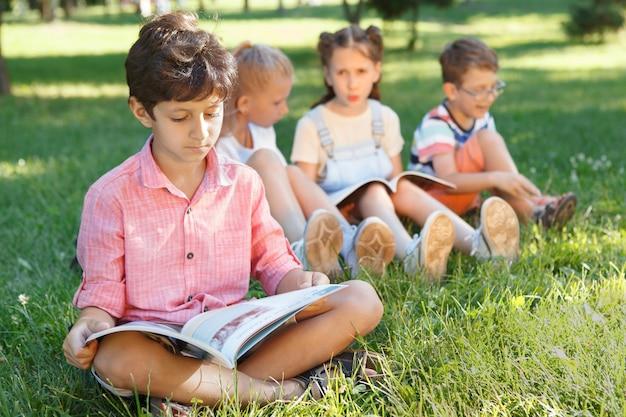 Jonge jongen die een boek leest, zittend op het gras in het park terwijl zijn vrienden praten