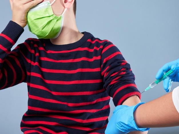 Jonge jongen die een chirurgisch masker draagt dat wordt gevaccineerd geïsoleerd op grijs, vaccinatieconcept