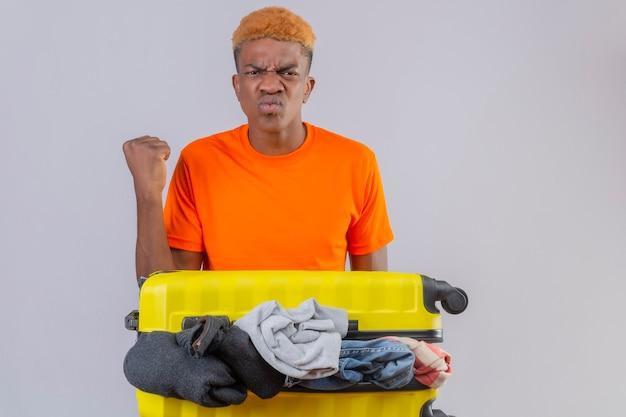 Jonge jongen die een oranje t-shirt draagt en zich met een reiskoffer vol kleren bevindt, ontevreden met fronsend gezicht, gebalde vuist over witte muur