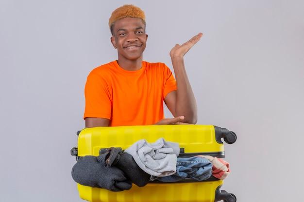 Jonge jongen die een oranje t-shirt draagt en zich met een reiskoffer vol kleren optimistisch en vrolijk glimlachend opheft, arm van zijn hand over witte muur