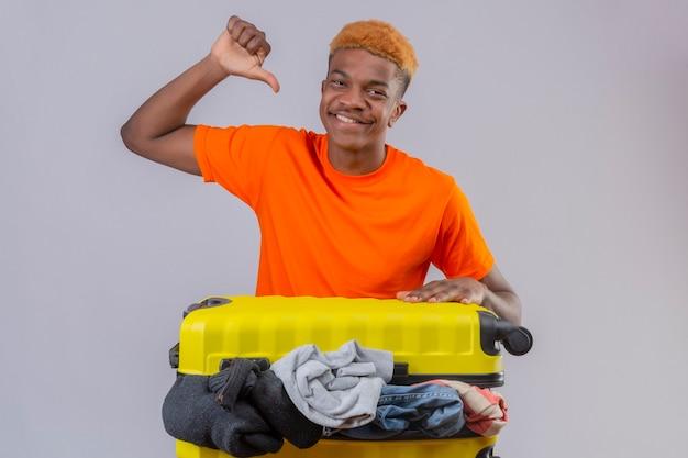 Jonge jongen die een oranje t-shirt draagt en zich met een reiskoffer vol kleren optimistisch en vrolijk lachend naar zichzelf richt met duim over witte muur