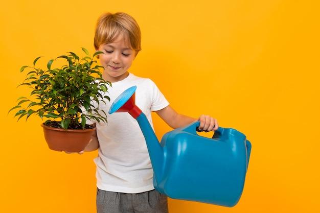 Jonge jongen die een pot met een plant en een gieter op een oranje muur