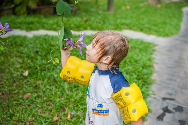 Jonge jongen die een tropische stam in de tuin houdt die en het bloemhoofd kijkt ruikt