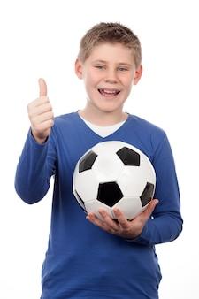 Jonge jongen die een voetbalbal op witte ruimte houdt