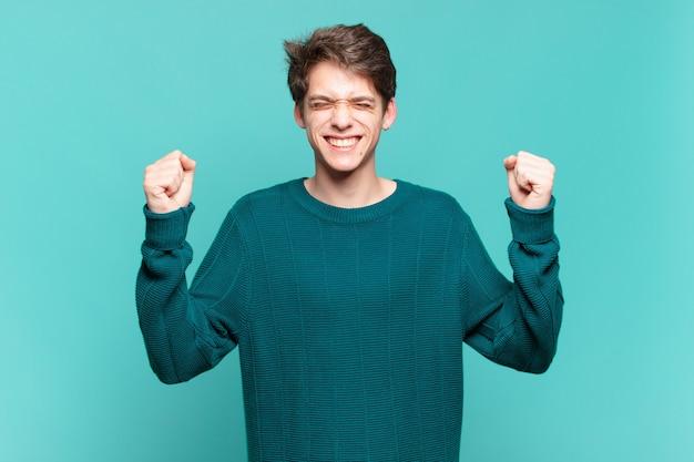 Jonge jongen die er extreem blij en verrast uitziet, succes viert, schreeuwt en springt