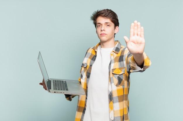 Jonge jongen die er serieus, streng, ontevreden en boos uitziet met een open palm die een stopgebaar maakt. laptopconcept