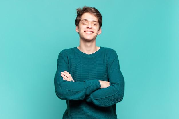 Jonge jongen die eruitziet als een gelukkige, trotse en tevreden presteerder die lacht met gekruiste armen