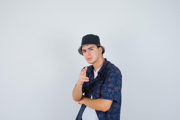 Jonge jongen die geweergebaar naar camera toont, hand onder elleboog in wit t-shirt, bloemenoverhemd, pet houdt en zelfverzekerd kijkt, vooraanzicht.