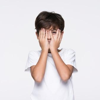 Jonge jongen die gezicht behandelt met handen