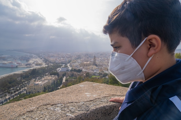 Jonge jongen die gezichtsmasker draagt en zijdelings naar de stad malaga in spanje kijkt.