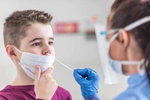 Jonge jongen die gezichtsmasker over mond draagt, houdt stil terwijl verpleegster een monster uit zijn neus neemt met een wattenstaafje.