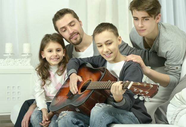 Jonge jongen die gitaar speelt voor zijn gezin