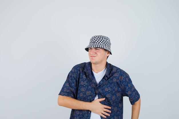 Jonge jongen die hand op buik houdt, buikpijn heeft in wit t-shirt, bloemenoverhemd, pet en uitgeput kijkt, vooraanzicht.
