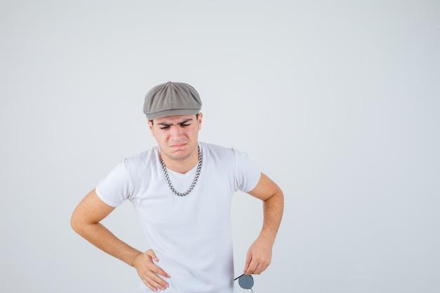 Jonge jongen die hand op taille in t-shirt, hoed houdt en pijnlijk kijkt. vooraanzicht.