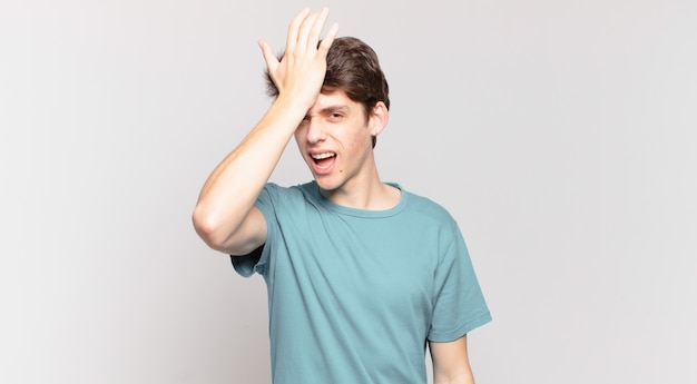 Jonge jongen die handpalm naar voorhoofd steekt en denkt oeps, na een domme fout te hebben gemaakt of zich te herinneren, voelt hij zich dom
