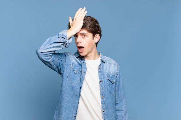 Jonge jongen die handpalm naar voorhoofd steekt en denkt oeps, na een domme fout te hebben gemaakt of zich te herinneren, zich dom voelen