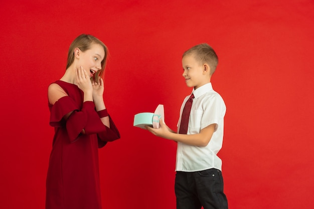 Jonge jongen die hartvormige doos geeft aan een meisje