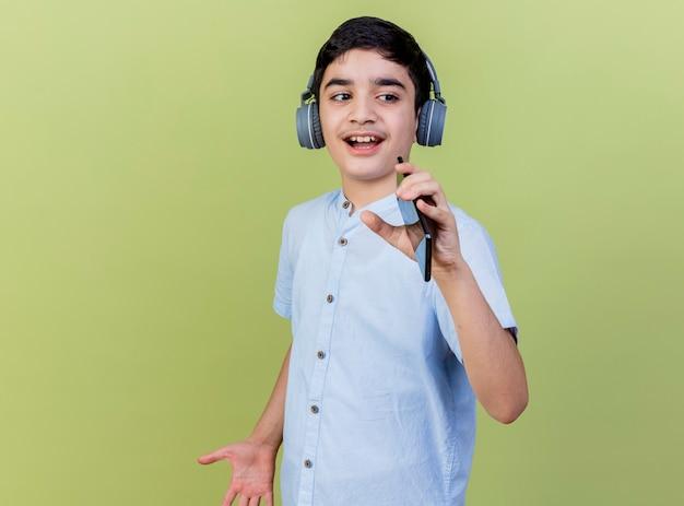 Jonge jongen die hoofdtelefoons draagt zingen die kant bekijken die mobiele telefoon als microfoon gebruiken die op olijfgroene muur wordt geïsoleerd