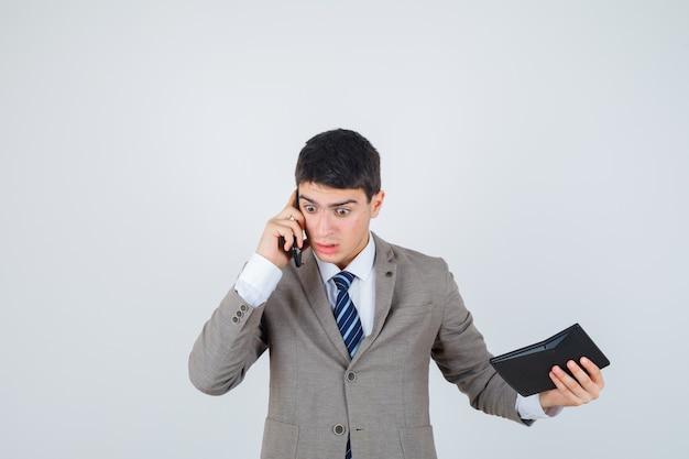 Jonge jongen die in formeel kostuum aan telefoon spreekt, calculator houdt en verbaasd, vooraanzicht kijkt.