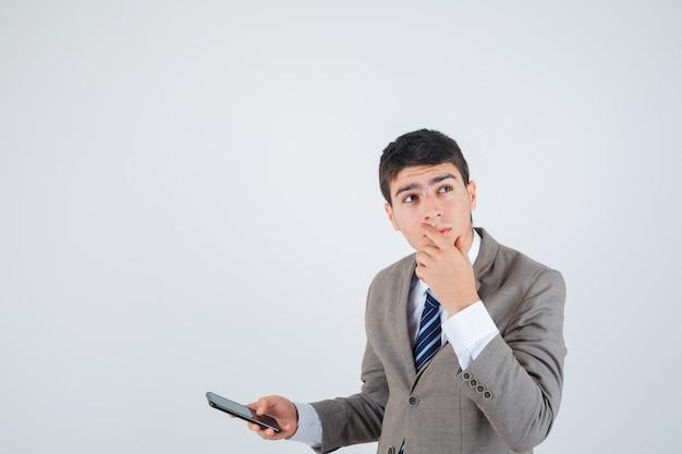 Jonge jongen die in formeel kostuum telefoon houdt, hand op kin legt, over iets nadenkt en peinzend, vooraanzicht kijkt.