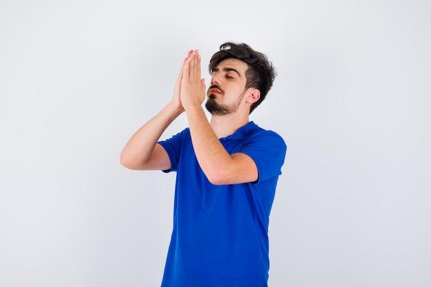 Jonge jongen die in gebed staat in een blauw t-shirt en er serieus uitziet. vooraanzicht.