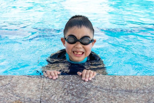 Jonge jongen die in pool zwemt.