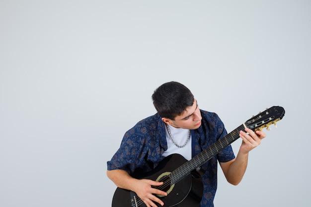 Jonge jongen die in t-shirt gitarist speelt terwijl hij aganist zit en op zoek is naar zelfverzekerd, vooraanzicht.
