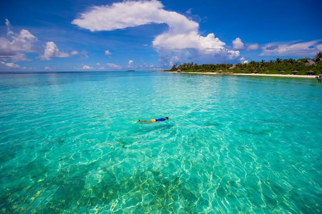 Jonge jongen die in tropische turkooise oceaan snorkelt