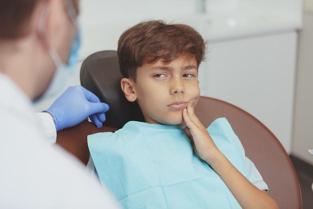 Jonge jongen die kiespijn heeft, die als tandvoorzitter zit tijdens tandonderzoek