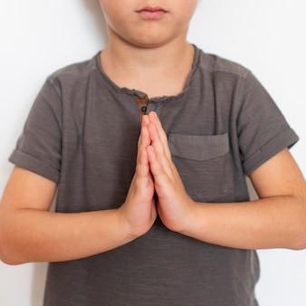 Jonge jongen die leert te bidden