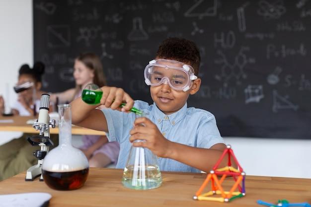 Jonge jongen die meer leert over scheikunde in de klas