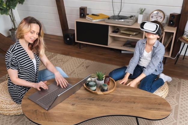 Jonge jongen die met virtuele werkelijkheid speelt terwijl de moeder werkt