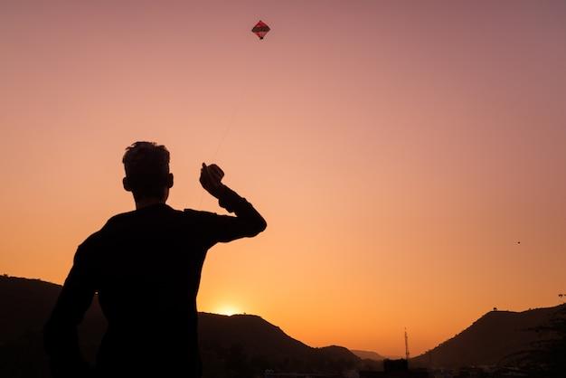 Jonge jongen die met vlieger bij zonsondergang speelt. achtergrondverlichting, kleurrijke lucht, achteraanzicht, rajasthan, india.