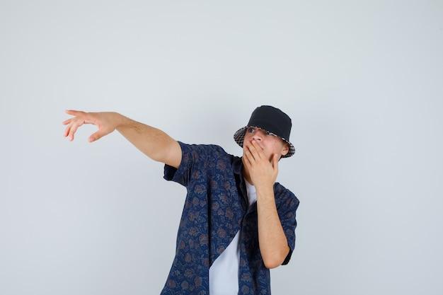 Jonge jongen die mond bedekt met hand, hand uitstrekt naar links in wit t-shirt, bloemenoverhemd, pet en verbaasd kijkt, vooraanzicht.