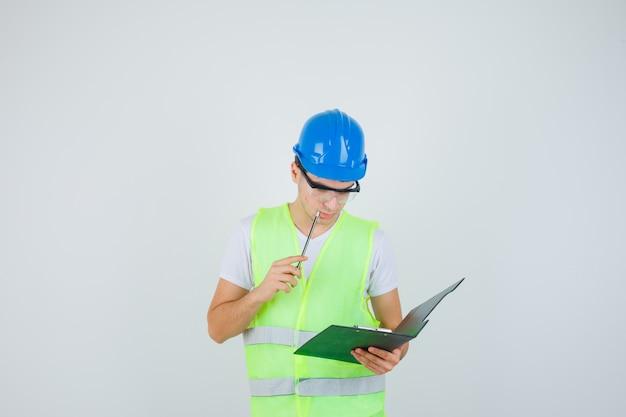 Jonge jongen die notities in klembord leest, pen dichtbij mond in bouwuniform zet en gericht, vooraanzicht kijkt.