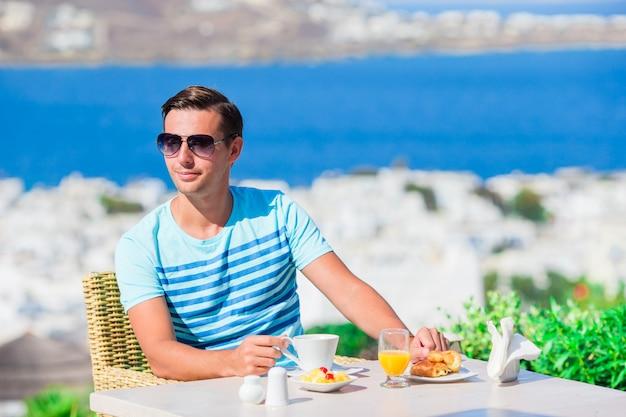 Jonge jongen die ontbijt heeft bij openluchtkoffie met verbazend uitzicht op mykonos-stad. mens die hete koffie op het terras van het luxehotel met overzeese mening drinken bij toevluchtrestaurant.