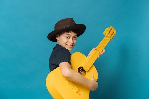 Jonge jongen die op blauwe muur in bruine hoed met een rand en een donkerblauwe t-shirt wordt geïsoleerd die gele gitaar en het leuke glimlachen houden. verjaardag vieren.