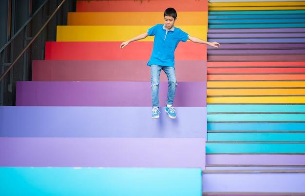 Jonge jongen die op de kleurrijke trederegenboog springen