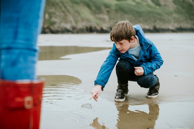 Jonge jongen die op een kwallen op de kust richt
