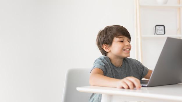Jonge jongen die op laptop kijkt