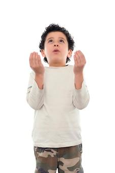 Jonge jongen die op witte achtergrond bidt