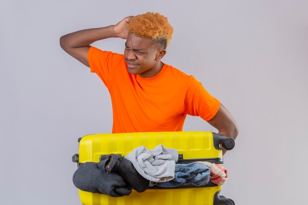 Jonge jongen die oranje t-shirt draagt dat zich met reiskoffer vol kleren bevindt die op zoek verward en zeer bezorgd over witte muur kijkt