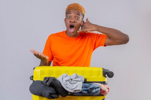 Jonge jongen die oranje t-shirt draagt die zich met reiskoffer vol kleren bevindt die verbaasd en verbaasd over witte muur kijken