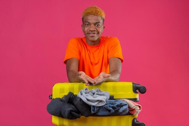 Jonge jongen die oranje t-shirt draagt die zich met reiskoffer vol optimistische en vrolijke kleren bevindt die over roze muur glimlachen