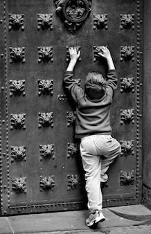 Jonge jongen die overladen, ouderwetse deur met grote kloppers probeert te beklimmen