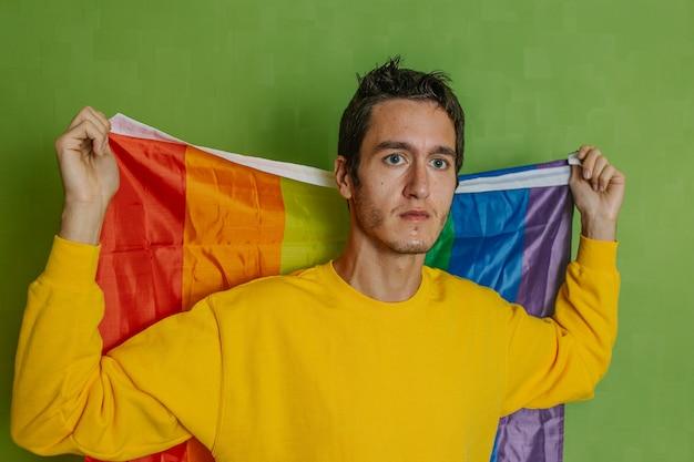 Jonge jongen die recht vooruit kijkt met een regenboogvlag op een groene achtergrond, lgbti, homo