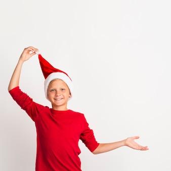 Jonge jongen die santahoed trekt