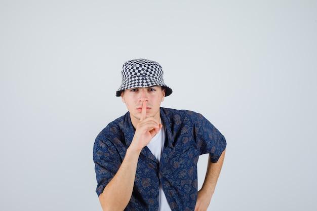 Jonge jongen die stilte gebaar toont, hand op taille in wit t-shirt, bloemenoverhemd, pet houdt en ernstig, vooraanzicht kijkt.