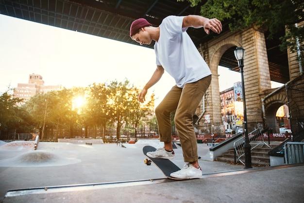 Jonge jongen die trucs met het skateboard in een vleetpark uitvoert